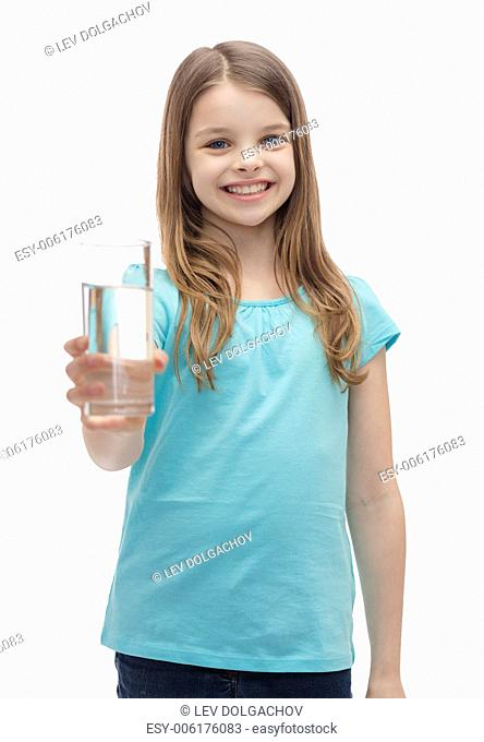 health and beauty concept - smiling little girl giving glass of water