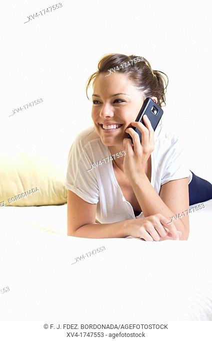 Pretty girl talk with mobile phone in the bedroom