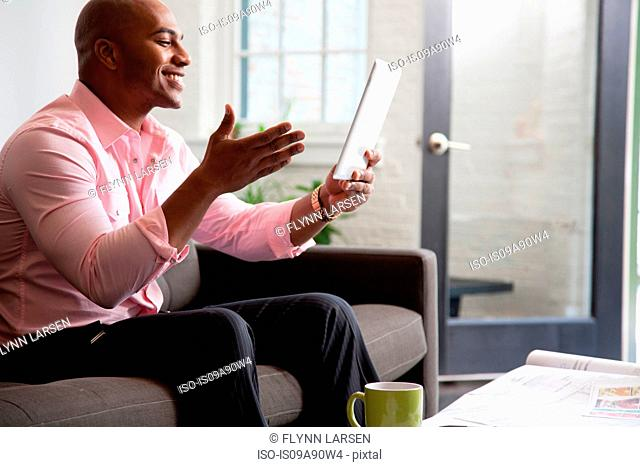 Mid adult man holding digital tablet on sofa and smiling