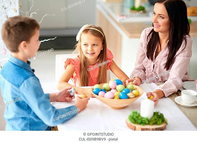 Girl with brother and mother preparing colourful easter eggs at dining table