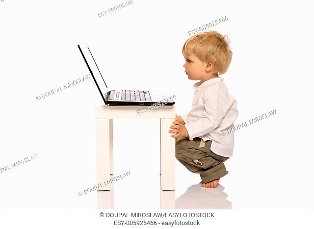Young boy looking at a laptop on a stool. Isolated on white background