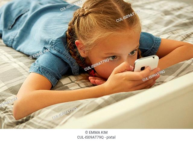 High angle view of girl lying on bed looking at smartphone