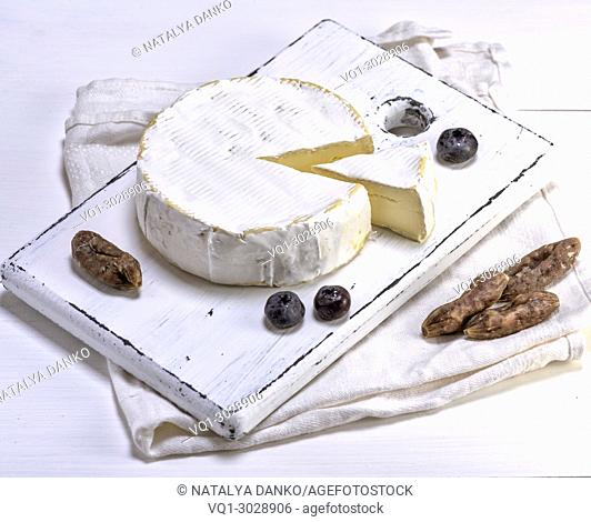 round Camembert cheese on a white wooden board, white wooden table, top view