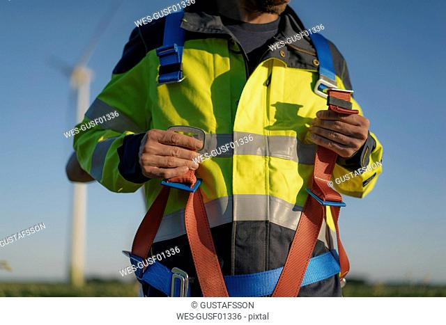Close-up of technician at a wind farm putting on climbing harness