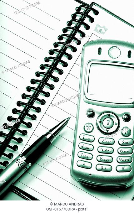 an opened notebook and a mobile on the table