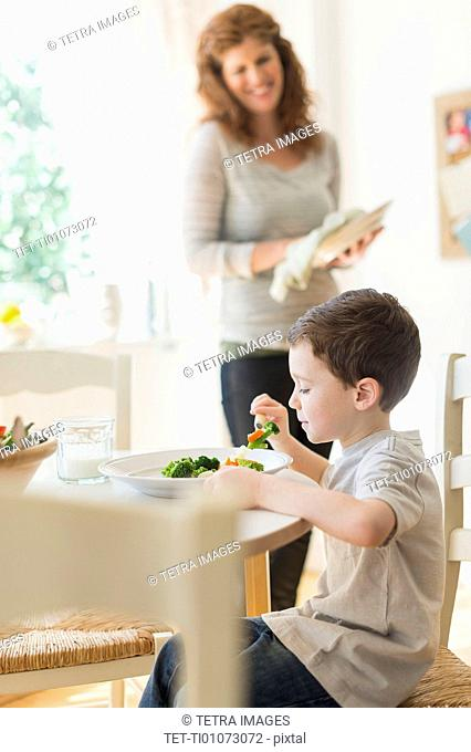 boy (6-7) eating healthy dinner, mother in background