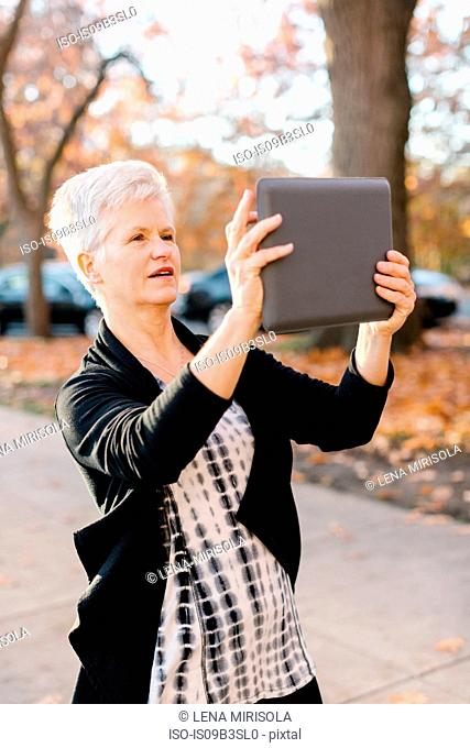 Senior woman outdoors, using digital tablet