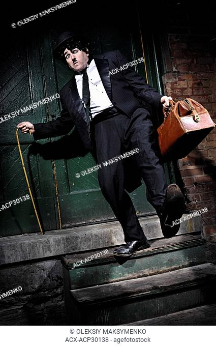 Man in a black suit with a bag Charlie Chaplin mime tripping and falling from a staircase. Artistic performance humorous concept