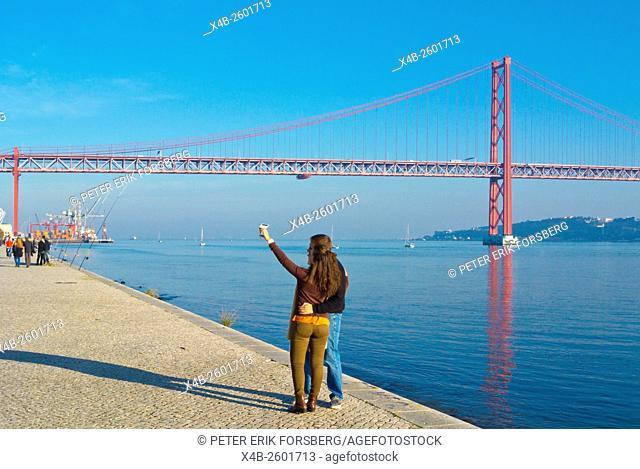 Couple taking a selfie, riverside Tagus, at Ponte 25 de Abril, Lisbon, Portugal