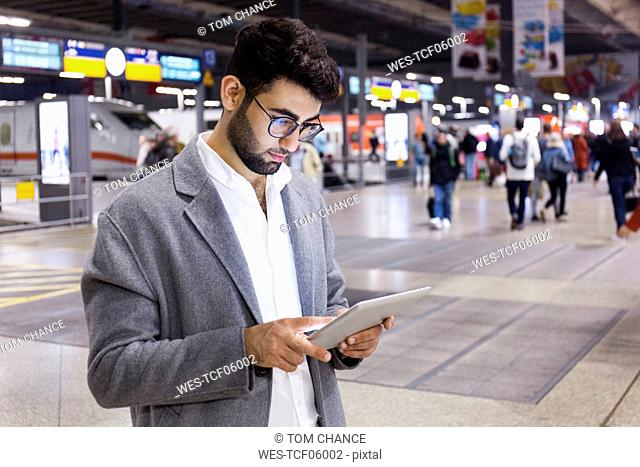Germany, Munich, young businessman using digital tablet at central station
