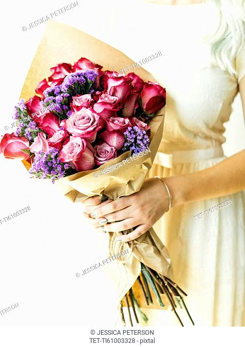 Woman holding bouquet with roses