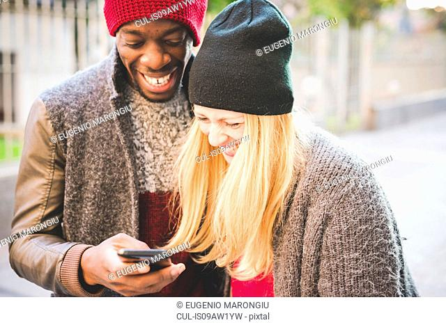 Couple smiling at message on smartphone