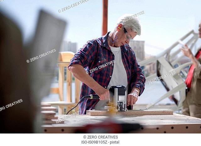 Mature female carpenter using sander in furniture making workshop