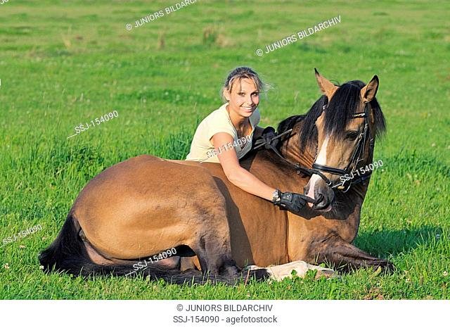 woman and Lusitano horse on meadow