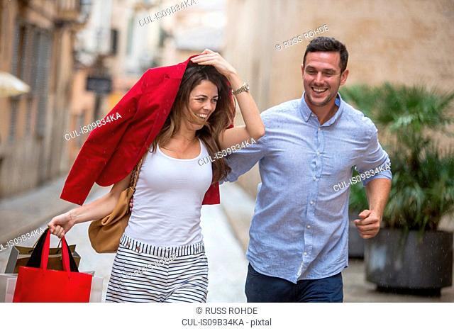 Couple laughing and running for shelter from rain
