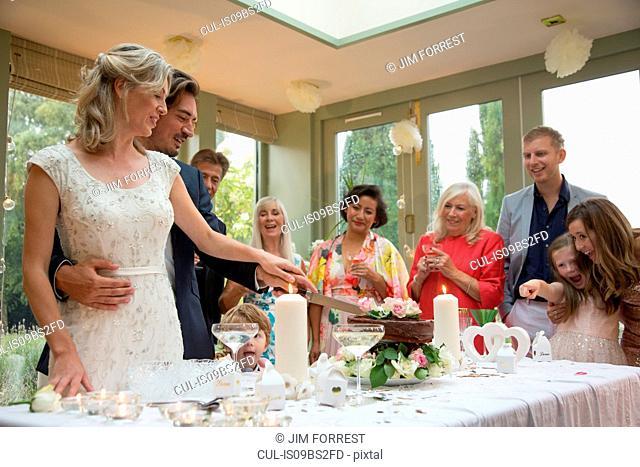 Newlyweds cutting wedding cake at reception