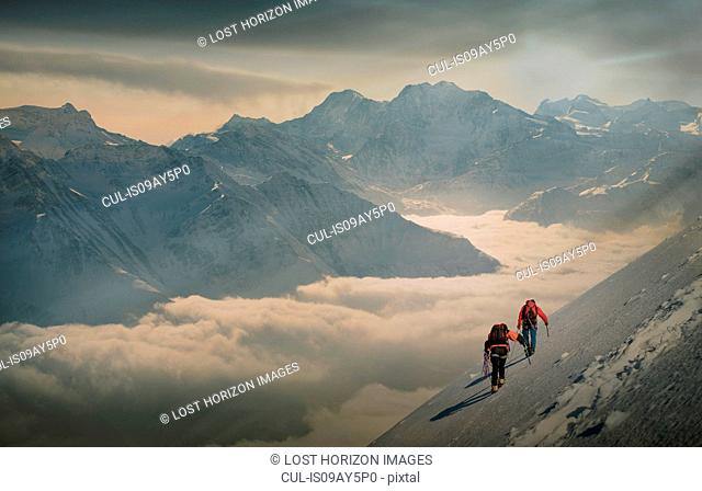 Two climbers on a snowy slope over a sea of fog in an alpine valley, Alps, Canton Wallis, Switzerland