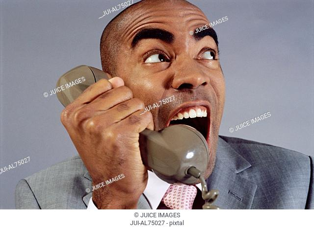 View of businessman screaming into phone