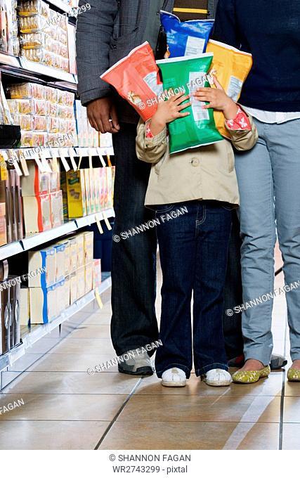 girl holding packets of crisps