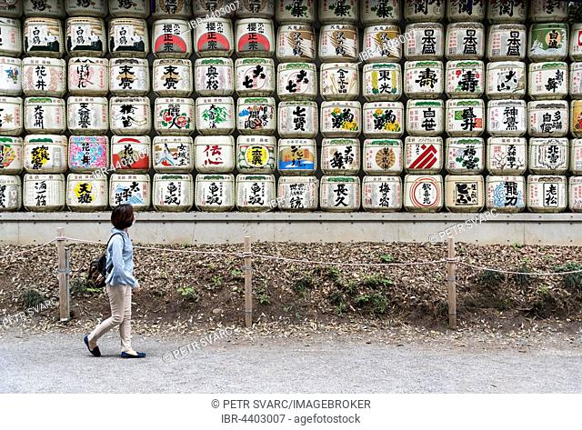 Woman walks pass sake barrels at Meiji Jingu Shrine, Tokyo, Japan