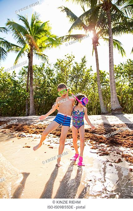 Two children fooling around on beach, wearing swimwear and snorkels