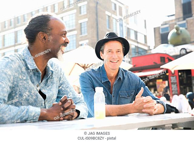Friends chatting at food market, London, UK