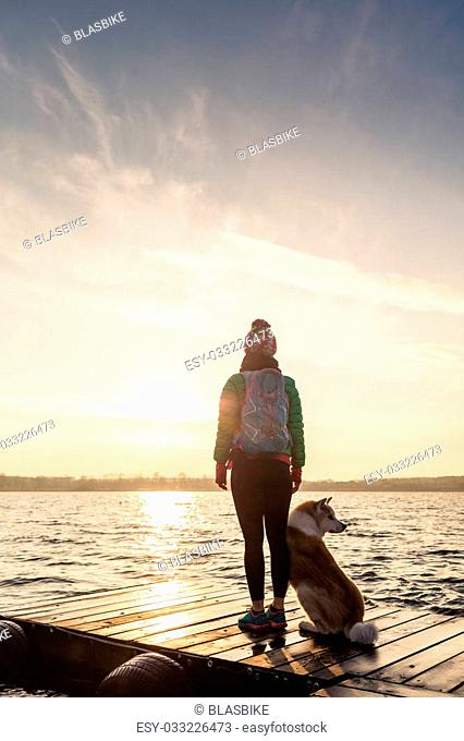 Woman with dog enjoy sunrise and lake, relaxing on bridge. Hiker or tourist looking at beautiful morning view with dog friend, inspirational landscape on beach
