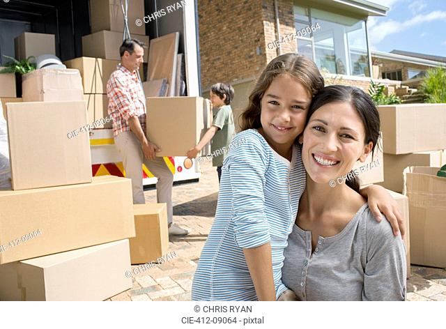 Mother and daughter smiling by moving van in driveway