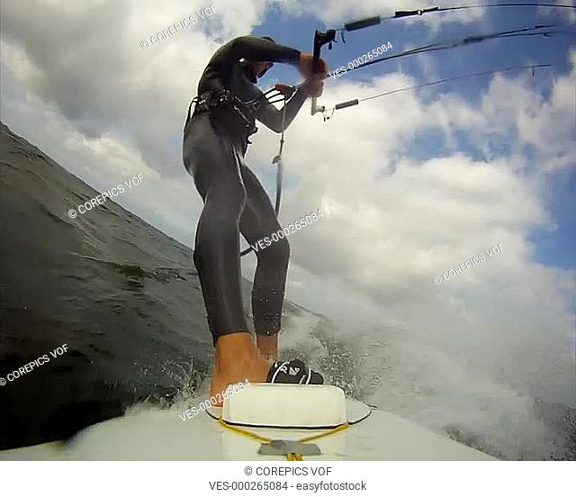 Young man in action, kite surfing at sea