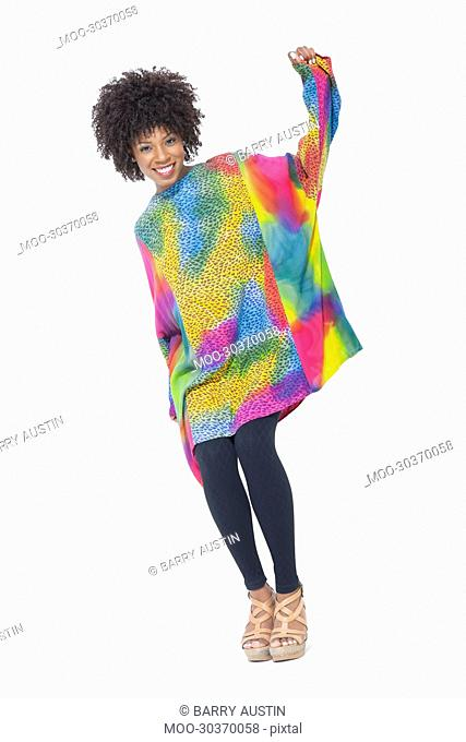 Full length portrait of an African American woman in dashiki standing over gray background