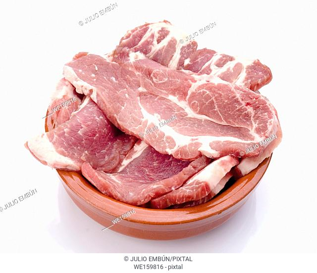 pork lean steaks in clay pot isolated on white background