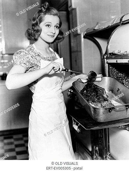 Young woman basting a goose in the kitchen All persons depicted are not longer living and no estate exists Supplier warranties that there will be no model...