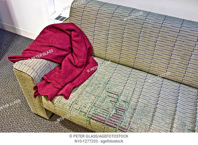 Red blanket on an old worn sofa