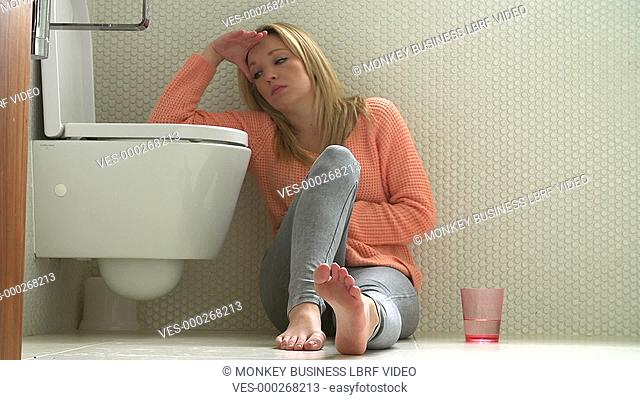 Teenage girl sits on floor of bathroom feeling unwell before being sick in toilet.Shot on Sony FS700 in PAL format at a frame rate of 25fps