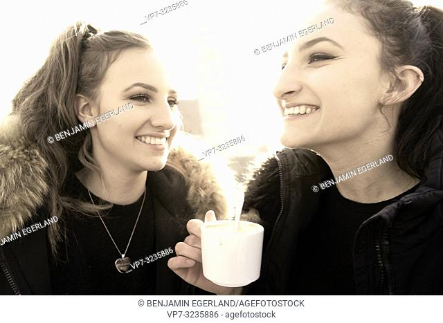 Two young sisters warm steaming coffee cup outdoors next to Frauenkirche, Marienkirche, in city Munich, Germany