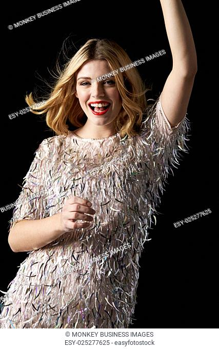 Glamorous blonde woman dancing with arms raised, waist up