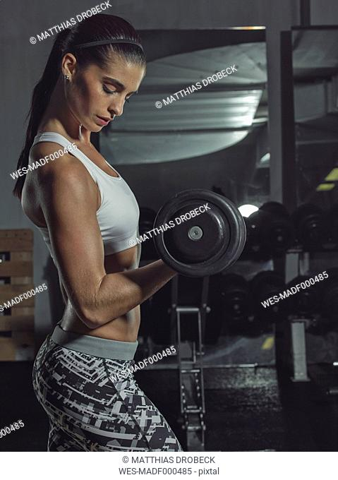 Portrait of a female athlete training with dumbbells in gym