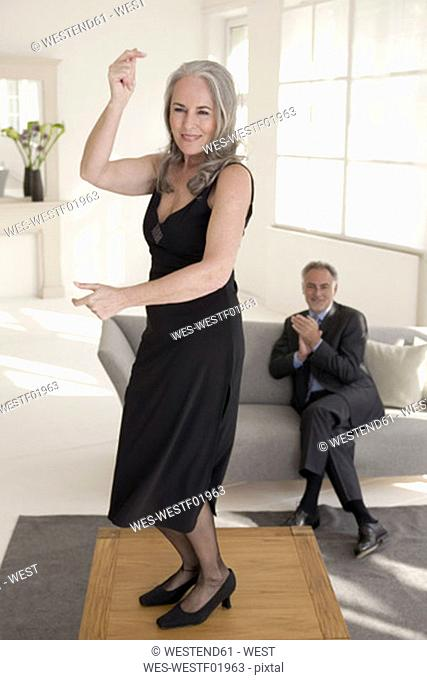 Mature man looking at woman dancing on table, smiling