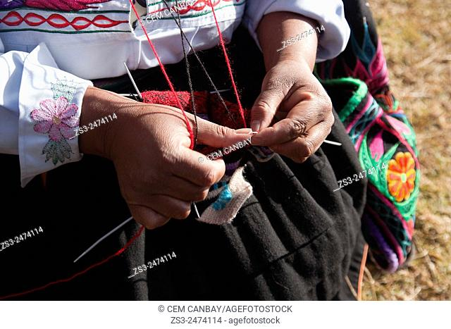 Indigenous woman in traditional dress knitting, Amantani Island, Titicaca Lake, Puno Region, Peru, South America