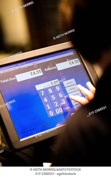 Information technology: A woman using a touch screen till in a cafe UK