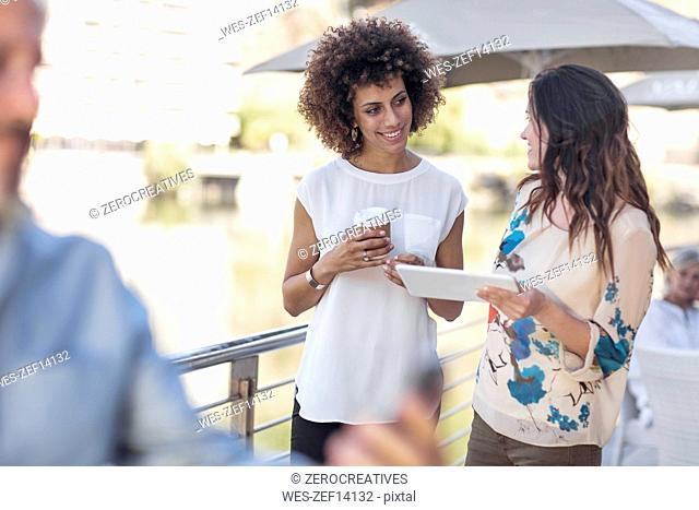 Businessman and woman having a meeting outdoors, using digital tablet