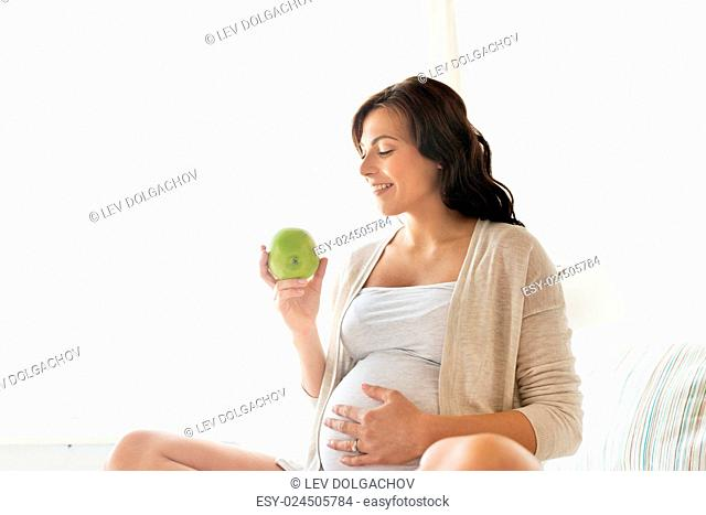 pregnancy, healthy food and people concept - happy pregnant woman eating green apple at home