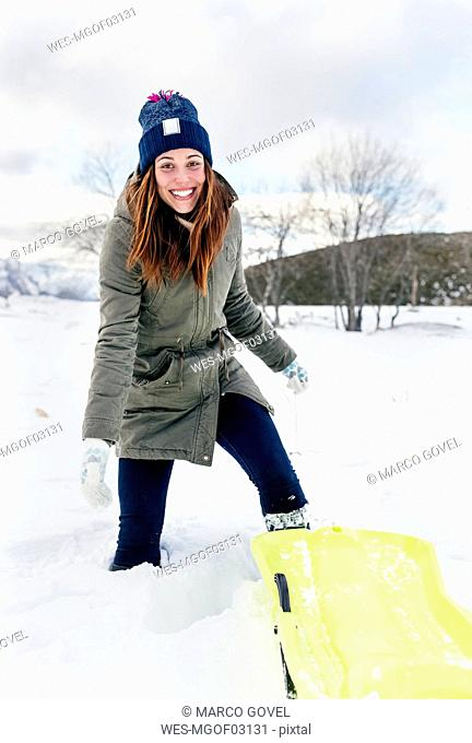Portrait of young woman having fun with sled in the snow