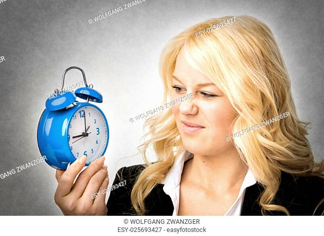 Unhappy blond woman unhappy with blue alarm clock