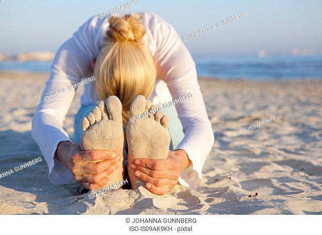Woman doing yoga prayer stretch on the beach