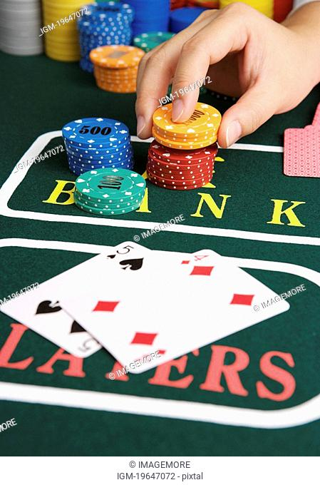 Man playing cards, placing bet with gambling chips, close-up