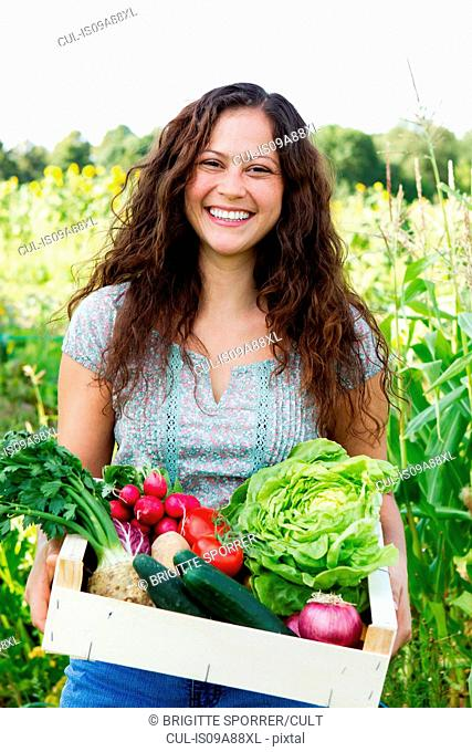 Portrait of young woman holding box of fresh vegetables in allotment