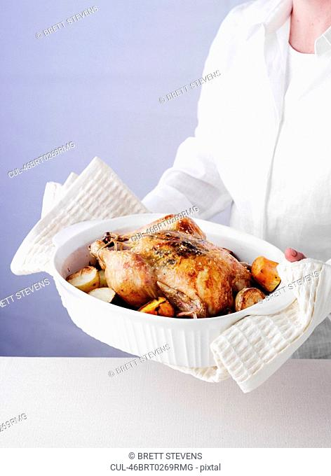 Woman holding dish of roast chicken