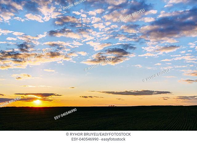 Natural Sunset Sunrise Over Field Or Meadow. Bright Dramatic Sky And Dark Ground. Countryside Landscape Under Scenic Colorful Sky At Sunset Dawn Sunrise
