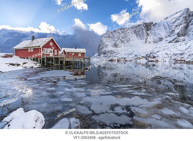 Traditional 'rorbu' houses with Renebringen peak in the background in winter. Reine, Lofoten district, Nordland county, Northern Norway, Norway